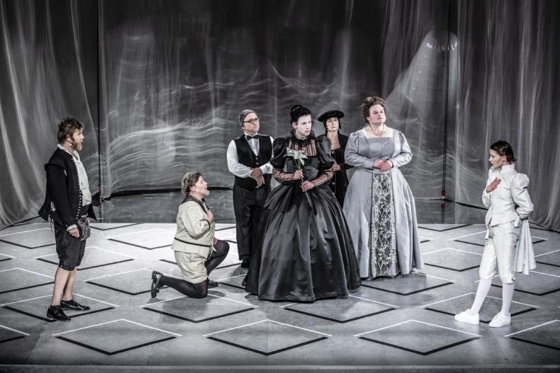 Scena zbiorowa. Cztery osoby stoją. Przed nimi klęczy mężczyzna. Wszyscy ubrani w szare, czarne stroje.