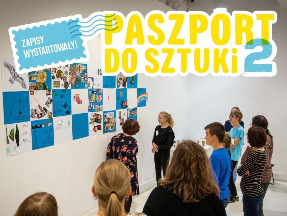 Grupa stoi przed białą ścianą. Na niej białe i niebieskie kartki z kolażami.